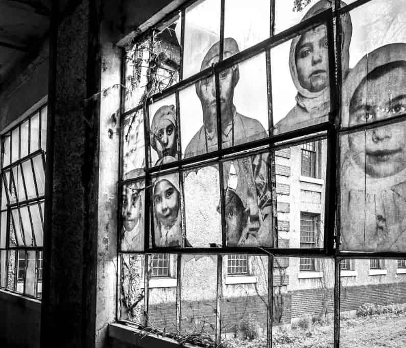 Cristalera del hospital abandonado de la Isla de Ellis con los rostros de inmigrantes tratados.